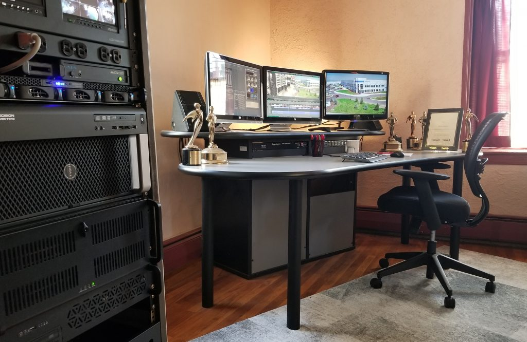 A picture from one of our editing suites, a station with rackmounted hardware, three monitors, and Avid Media Composer opened to a current project. There are several golden statue awards at the table for past productions.